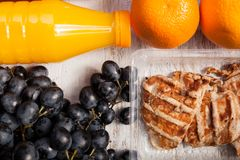 Lunch packed in different boxes. Healthy lunch of grilled chicken, cabbage, grape and juice packed in different boxes. Fresh and healthy eating on white wooden Stock Photography