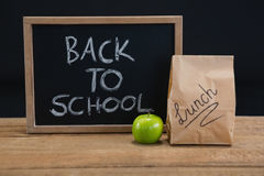 Lunch paper bag, green apple and slate with text back to school on wooden table. Against black background Stock Image