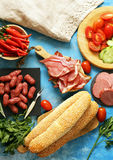 Lunch picnic table deli meats sausage, salami, parma, prosciutto bread and vegetables Royalty Free Stock Photo