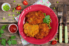 Lunch: pork chops with bread crust, green peas and tomatoes Royalty Free Stock Photo