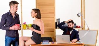 Lunch rozmowa Partnery biznesowi opowiada na przerwie na lunch podczas gdy gniewny kolega pracuje w tle koledzy m?odzi obrazy stock