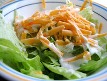 Lunch Salad. Lettuce with salad dressing and cheddar cheese royalty free stock image