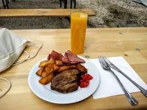 Lunch. Salami, steak potato, meat and orange juice Royalty Free Stock Photo