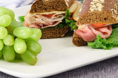 Lunch sandwich. Just made fresh honey wheat and oats bread sandwich with organic grapes Royalty Free Stock Photos