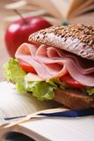 Lunch: sandwich with ham and red apple on notebook Stock Image