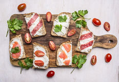 Lunch with sandwiches with salami and smoked red fish with parsley leaves and curd cheese wooden rustic background top view clo Royalty Free Stock Images