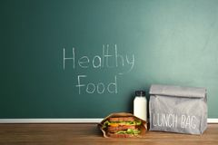 Lunch for school child on table near chalkboard. With written Healthy Food royalty free stock photography