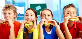 Lunch in school. Four schoolkids looking at camera while having lunch during break Stock Photography