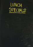 Lunch specials on blackboard in vertical. Lunch specials title handwritten with white chalk on blackboard, copy space below, restaurant advertisement Royalty Free Stock Photos