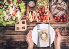 Lunch at the table with different food, women`s hands with a plate stock images