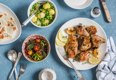 Lunch table. Lemon thyme baked chicken, boiled potatoes with green peas, salad with lentils and tomatoes, flatbread on a blue back royalty free stock image