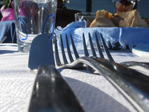 Lunch table setting outdoors in white-blue colors . Forks and knife in foreground Royalty Free Stock Image
