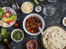 Lunch table - tortilla, stewed beans, vegetables, cheese, spicy green chile sauce. Delicious, vegetarian food. On a dark backgroun Royalty Free Stock Images