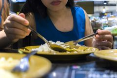 Lunch at a Thai restaurant. A woman eats rice with vegetables and soup stock photography