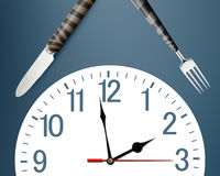 Lunch time. Concept, clock in plate, knife and fork Stock Image