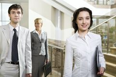 Lunch- time. Young brunette businesswoman with the black case in her hand looking at camera, thinking businessman in white suit and cute smiling woman moving on Royalty Free Stock Image