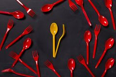 Lunch time background with colorful disposable cutlery. Lunch time background. Yellow disposable spoon and fork as clock arrows showing dinner time at black Stock Photos