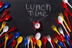 Lunch time written on blackboard with chalk. Lunch time background. Red alarm clock and lots of disposable colorful cutlery on blackboard with inscription Stock Image