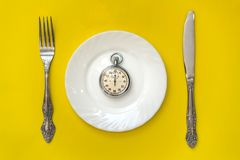 Lunch time concept. Clock with knife and fork. On yellow background Stock Photos