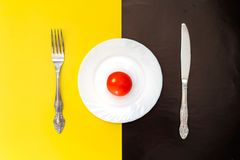 Lunch time concept. Plate with knife and fork. Lunch time or diet concept. Plate with knife and fork on black and yellow background Royalty Free Stock Images