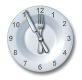 Lunch Time Dining. Concept with a fork and knife on a plate in the shape of a clock with numbers as a symbol of eating time or fast food entertainment in the Stock Photography