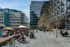 Lunch time at Exchange Square, London, with office workers. Exchange Square, Liverpool Street, London, UK - April 6, 2018: Lunch time on a sunny day with office stock images