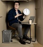 Cheerful manager is feeling gladness at work. Lunch time. Full length portrait of happy young employee is sitting at table in cardboard office and holding clock stock photos