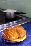 Lunch time in the kitchen. Bread on plate in kitchen with pot on stove in background Royalty Free Stock Photo