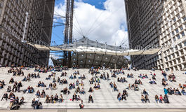 Lunch Time in La Defense. La Defense, France- April 19th, 2012: Image of various people having their frugal lunch on the steps under the Grand Arche in La royalty free stock photo