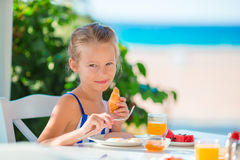 Lunch time. Little girl having breakfast at outdoor cafe with sea view Stock Photos
