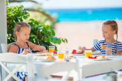 Lunch time. Little girls having breakfast at outdoor cafe with sea view Stock Image