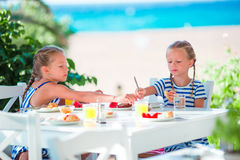Lunch time. Little girls having breakfast at outdoor cafe with sea view Royalty Free Stock Images