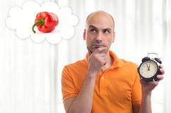Lunch time. Man dreams about food. Lunch time. Man holding alarm clock and dreams about food Royalty Free Stock Image