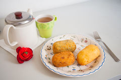 Lunch time. Plate with baked potato with cheese and teapot, lunch time Stock Photos