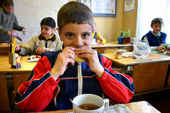 Lunch time at a rural school, schoolboy eats lunch Stock Photo