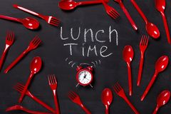 Lunch time written on blackboard with chalk. Lunch time background. Red alarm clock and lots of disposable cutlery on blackboard with inscription written with Royalty Free Stock Photography