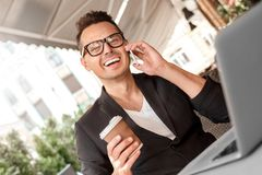 Lunch time. Young man in suit and glasses sitting at cafe on city street with laptop with cup of coffee talking on stock photos