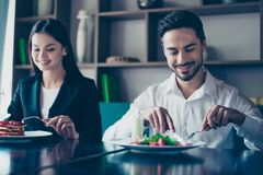 Lunch together. Two young cute lovers are sitting in a fancy res. Taurant, wearing smart outfits and eating delicious salad and a dessert, smiling Stock Photography