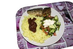 Lunch on a tray.Rice with fish and salad on a plate. Lunch on a tray on a white background.Rice with fish and salad on a plate stock images