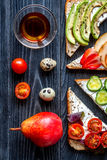 Lunch with triangle sandwiches on dark table background top view Royalty Free Stock Photos