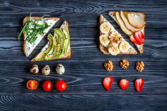Lunch with triangle sandwiches on dark table background top view Stock Photography