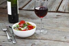 lunch Vin i ett exponeringsglas och en sallad av nya grönsaker Begrepp: äta i en restaurang Arkivbild