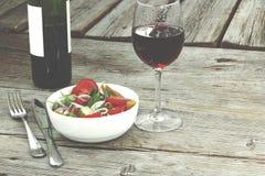 lunch Vin i ett exponeringsglas och en sallad av nya grönsaker Begrepp: äta i en restaurang fotografering för bildbyråer