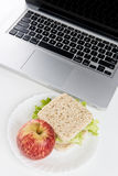 Lunch at work. Place near laptop on white background Stock Photos