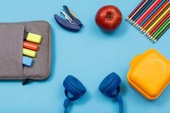 Lunchask, färgblyertspennor, äpple, hörlurar, äpple- och påse-blyertspenna fall med färgfiltpennor och markör på blå bakgrund arkivfoto