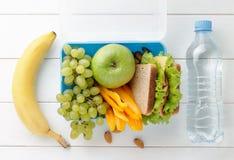 Lunchask med den olika sunda mellanmål och flaskan av vatten på den vita trätabellen Royaltyfri Bild
