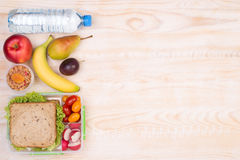 Lunchbox with sandwich, fruits, vegetables, and water Stock Images
