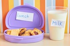Lunchboxen med kex och ett exponeringsglas av mjölkar på tabellen arkivbild
