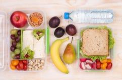 Lunchboxes med smörgåsar, frukter, grönsaker och vatten royaltyfri foto