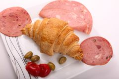 Luncheon and croissant. Mortadella luncheon meat with croissant, olive and tomato as breakfast Stock Photo